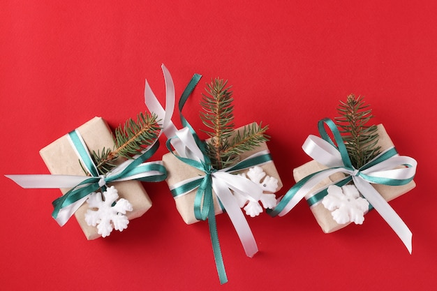 Three christmas giftboxs with green and white ribbon on red surface