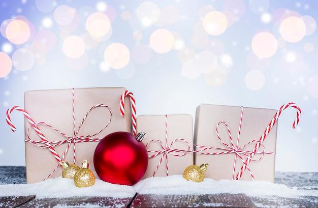 나무 테이블에 세 개의 크리스마스 선물과 크리스마스 장식