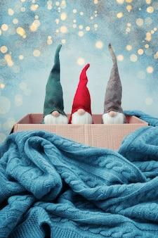 Три рождественских гнома разных цветов в открытой коробке, вязаное одеяло