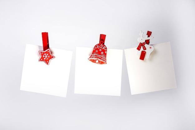 Три рождественские заметки с красными прищепками на заднем плане. копировать пространство