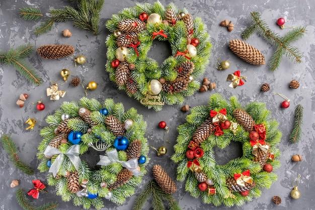 Три рождественский венок с ели, сосновые шишки, шарики, ленты и желуди на бетонной поверхности с копией пространства.