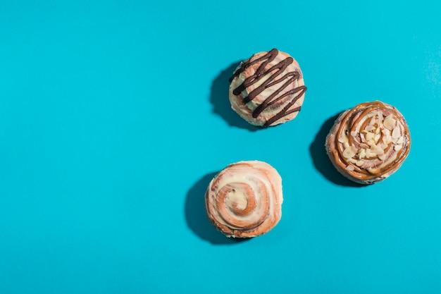 Три булочки cinnabon на синем фоне с жесткими тенями. американская классическая булочка.