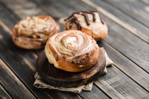 Три булочки cinnabon на деревянной доске с салфеткой на темном фоне. американская классическая булочка.