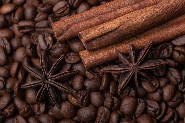 コーヒー豆を背景にした3本のシナモンスティックとスターアニス