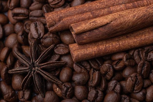 Три палочки корицы и звездчатый анис на фоне кофейных зерен