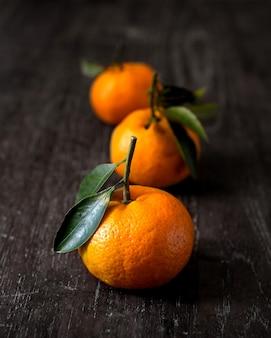 Три цитрусовых - свежий спелый апельсин на деревянном столе. темная фотография