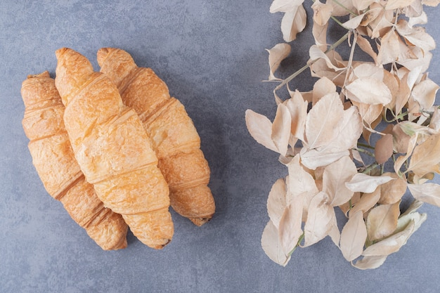 Three classic french croissant with decorative leaves over grey background.