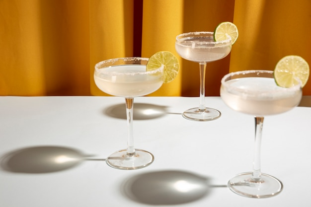 Three classic margarita drink with lime and salt in saucer glasses on table