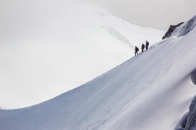 Три альпиниста на вершине снежной вершины