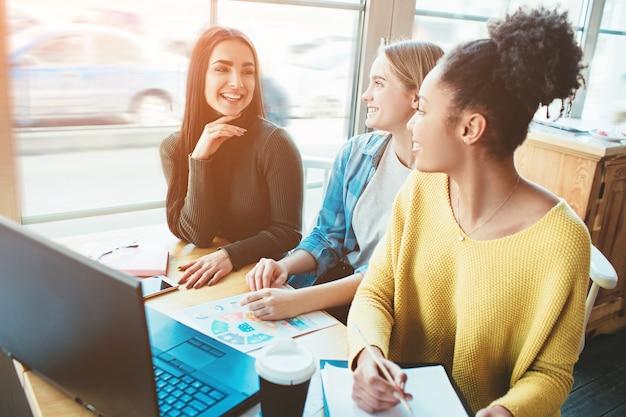 Трое близких сидят вместе за одним столиком в кафе и смотрят в экран ноутбука.