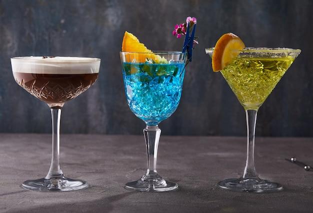 Три коктейля эспрессо мартини, блю кюрасао и тея, стоящие в ряд на сером столе