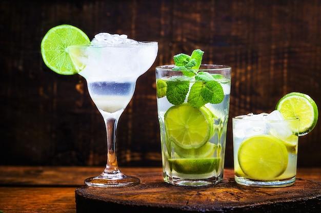 Three cocktails of lemon alcohol. brazilian caipirinha, cuban mojito and margarita frozem.