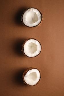 茶色の無地の背景、抽象的な食品トロピカルコンセプト、トップビューで行に3つのココナッツフルーツ