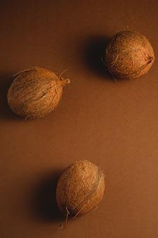 鮮やかな茶色の無地の背景、トロピカルコンセプト、トップビューで3つのココナッツフルーツ
