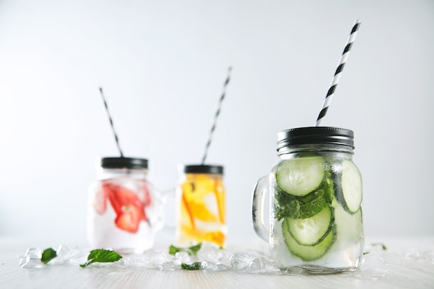 Three cold refreshment beverages from strawberry, orange, lime, mint, ice and sparkling water in rustic jars with drinking straws inside
