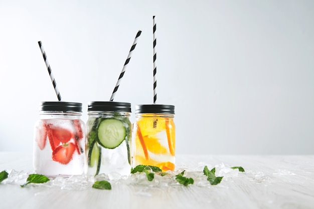Three cold refreshment beverages and sparkling water in rustic jars with drinking straws inside