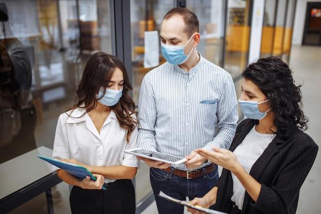 医療用マスクを着用した3人の同僚が、コロナウイルスのパンデミック検疫中にオフィスの廊下でビジネスについて話し合っています。