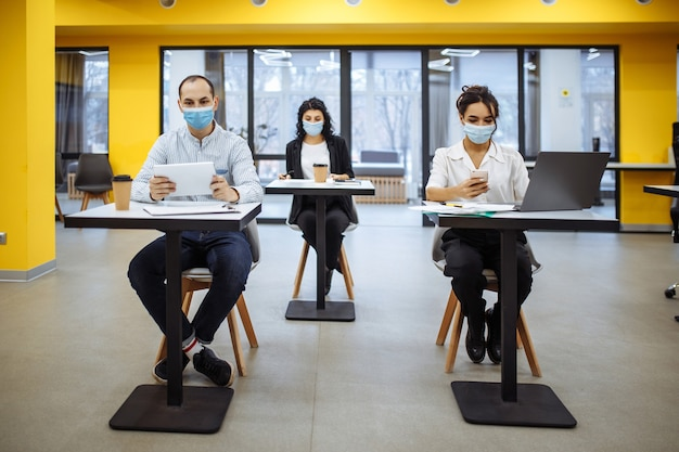 Three colleagues work together at an office keeping social distance weaing medical masks.