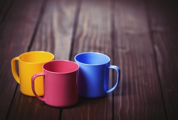 木製のテーブルの上の3つの色のコップ
