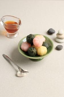 삼색 송편꿀떡을 대나무 찜통과 나무그릇에 담았습니다. 송편은 설날이나 한국의 감사절에 먹는 한국 전통 음식입니다.
