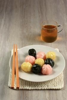 하얀 접시와 나무 접시에 담긴 삼색 송편 꿀떡. 송편은 설날이나 한국의 감사절에 먹는 한국 전통 음식입니다.