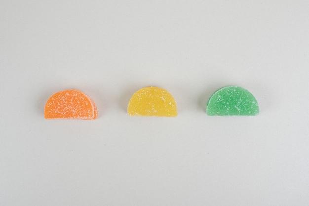 Три цветные желейные конфеты на белой поверхности