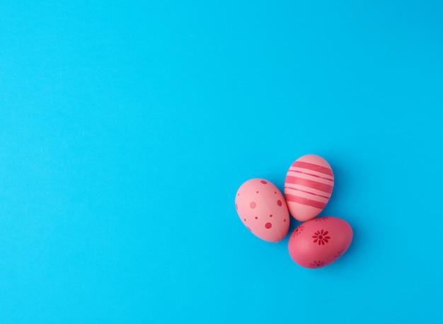Три цветные розовые пасхальные яйца на синем фоне