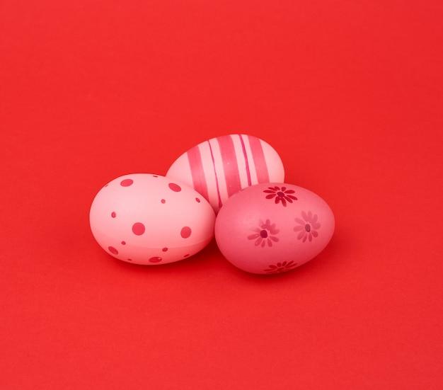 Три цветные розовые пасхальные яйца на красном фоне