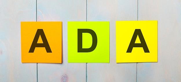 水色の木製の背景にadaamericans with disabilitiesactというテキストが付いた3色のステッカー