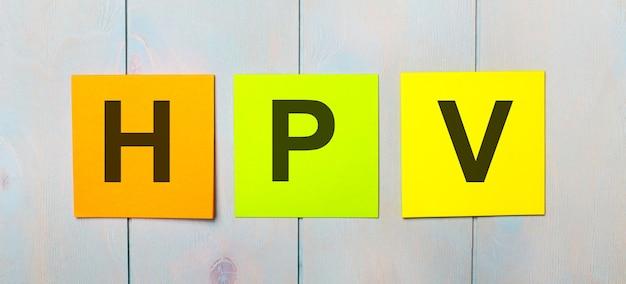 水色の木製の表面にhpvというテキストが付いた3色のステッカー