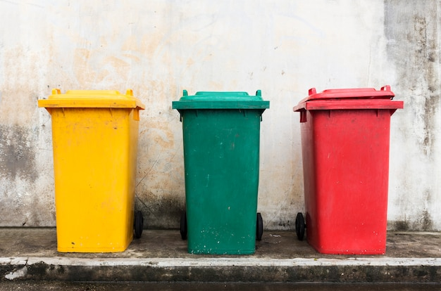 Three colorful bins with brick wall background