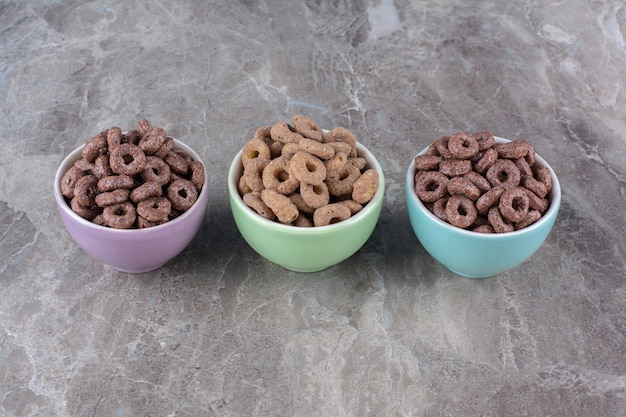 Three colorful bowls of chocolate cereal rings for breakfast .