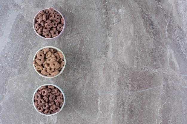 Tre ciotole colorate di anelli di cereali al cioccolato per la colazione.