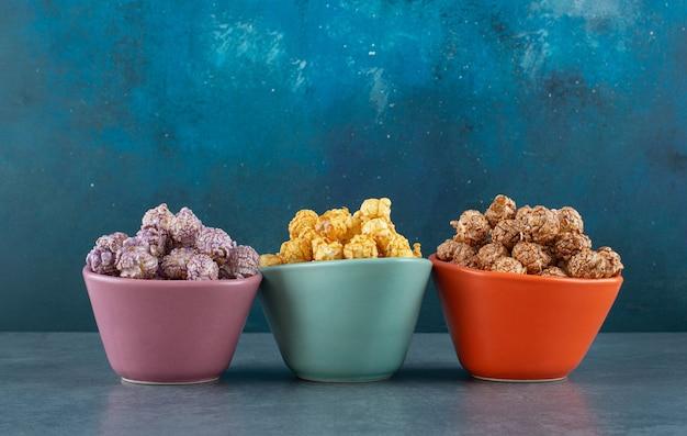 Tre ciotole colorate piene di vari gusti di popcorn su sfondo blu. foto di alta qualità