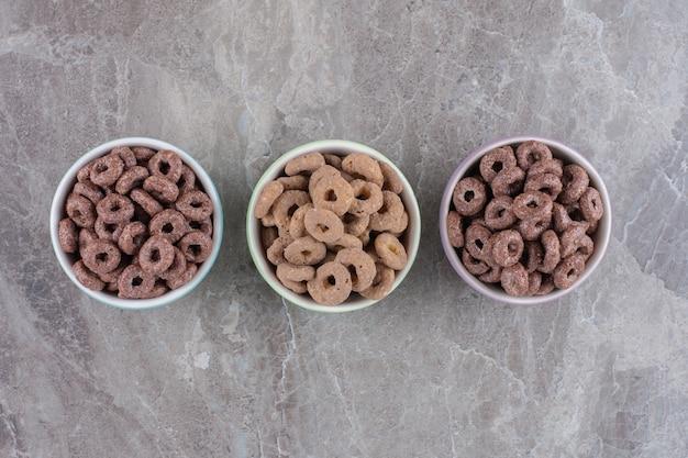 朝食用のチョコレートシリアルリングの3つのカラフルなボウル。