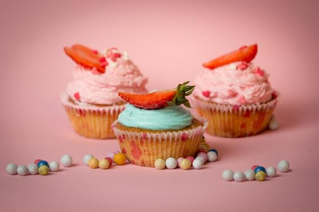 Три красочных кекса с клубникой на розовом фоне с конфетами
