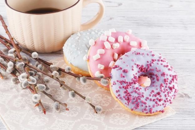 세 가지 다채로운 도넛, 커피 한잔과 흰색 테이블에 버드 나무