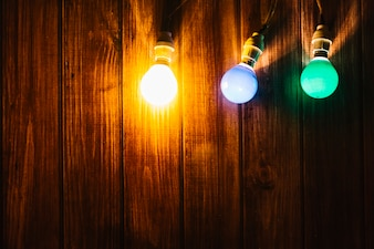 Three colorful lights on wooden background