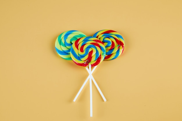 Three colorful lollipops on orange background.