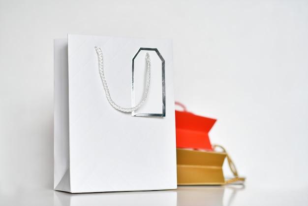 白い背景の上の3つのカラフルな紙のショッピングバッグ