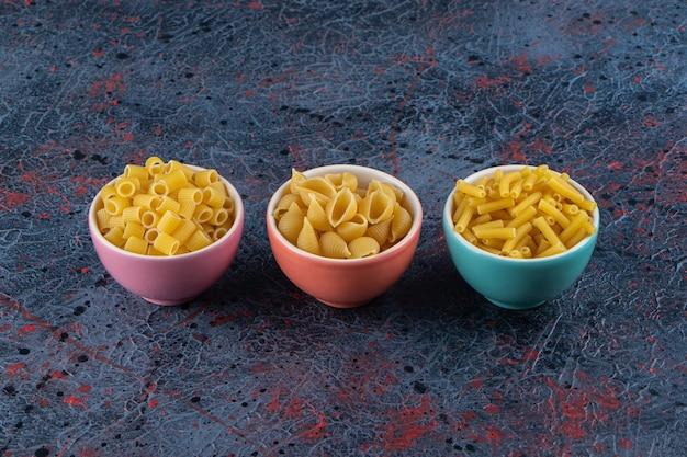 Tre piatti colorati con diversi tipi di pasta cruda su uno sfondo scuro.