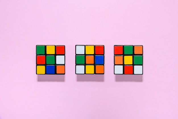 Three colorful rubiks cubes on a pink table
