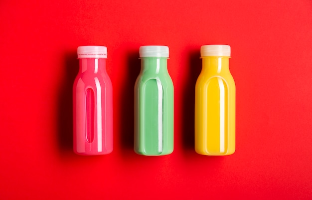 Three colorful smoothies on red background
