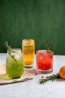 灰色のテーブルの上のグラスで3つのカラフルな夏のカクテル。新鮮な夏の飲み物の品揃え。