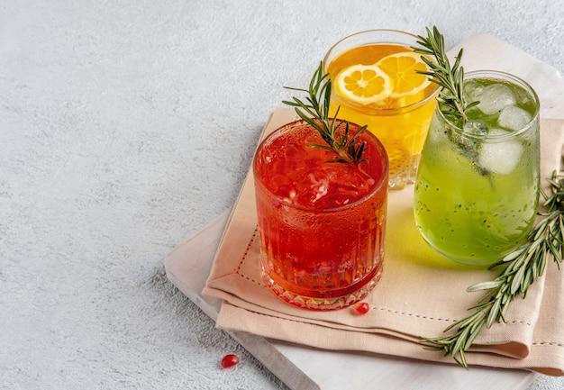 白いテーブルの上のグラスで3つのカラフルな夏のカクテル。新鮮な夏の飲み物の品揃え。