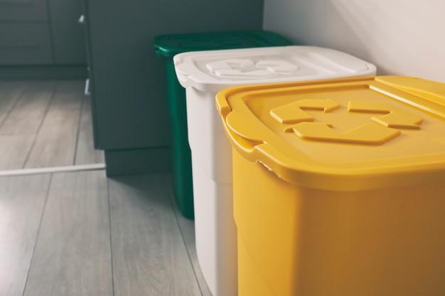 Три разноцветных мусорных бака для сортировки мусора. для пластика, стекла и бумаги