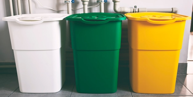 ゴミを分別するための3つのカラフルなゴミ箱。プラスチック、ガラス、紙用