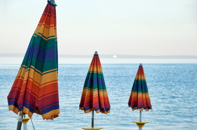 Three colorful umbrellas in front of the sea