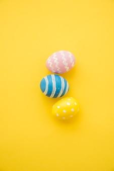 Три красочные пасхальные яйца на желтом столе