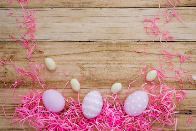 Three colourful easter eggs with decorative straw on table